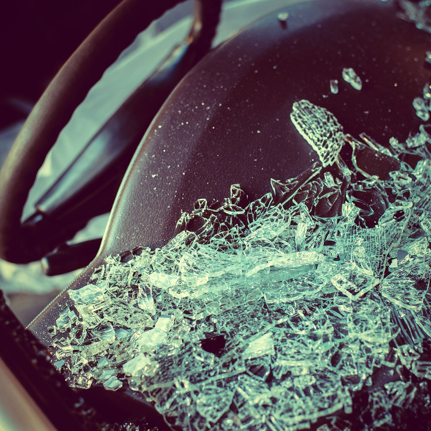 Close-up photo of a broken windshield laying on a dashboard